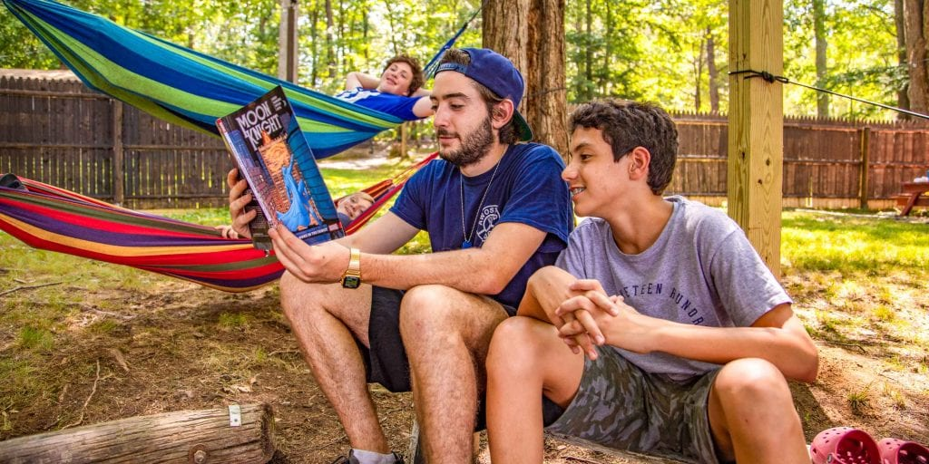 Camper and counselor enjoy a comic book
