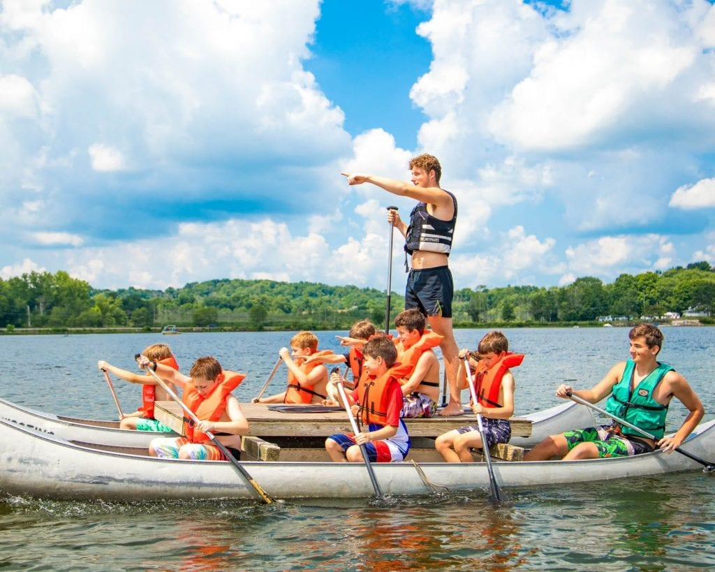 Group of campers rows boat while pointing forward