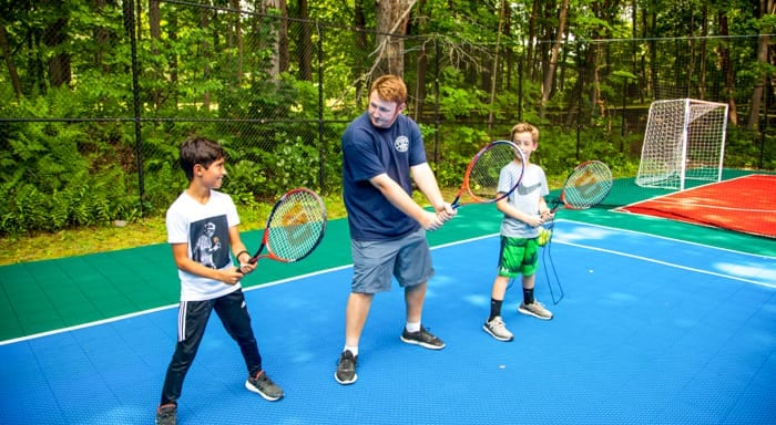 Instructor teaches campers to play tennis