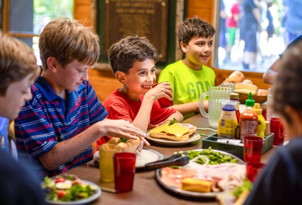 Group of boys eat a meal at summer camp