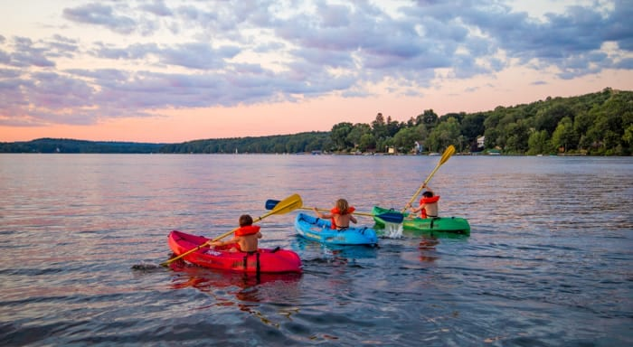 Campers kayak onto lake at sunset
