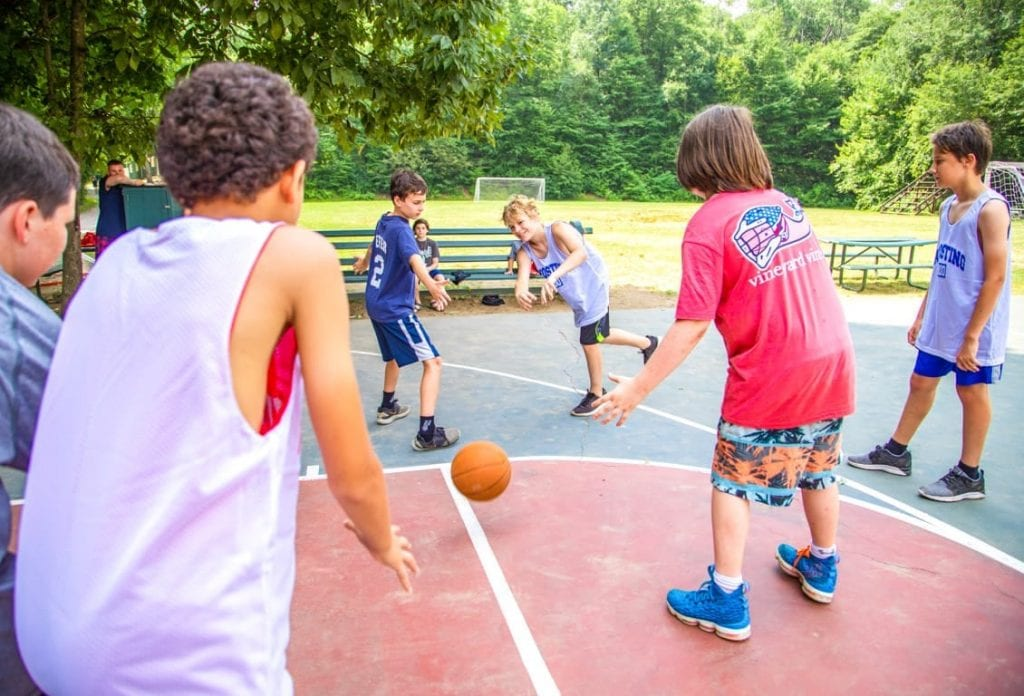 Group of boys playing basketball at summer camp