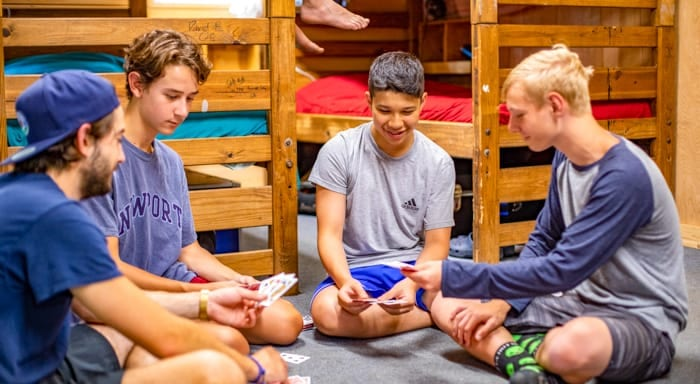Older campers play cards in their cabin