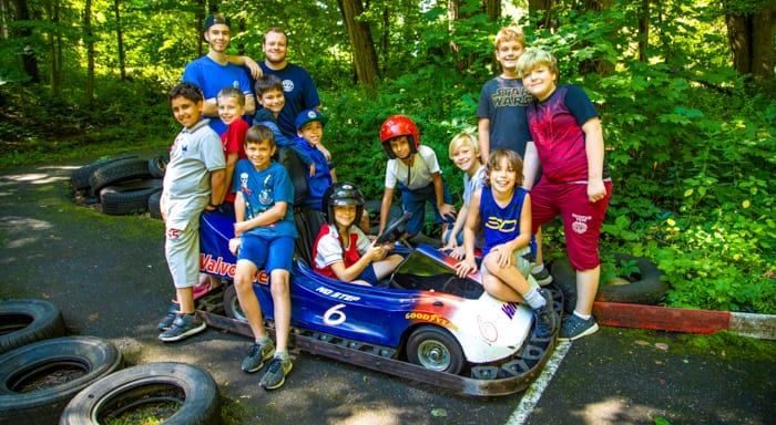 Campers pose for picture around go-kart