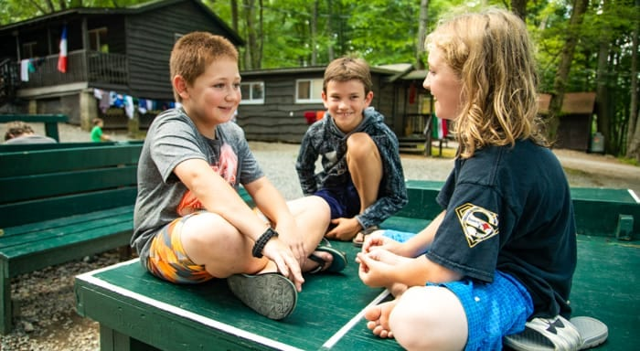 Campers sit on a ping-pong table to chat