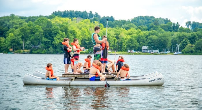 Campers stand on canoe catamaran on lake