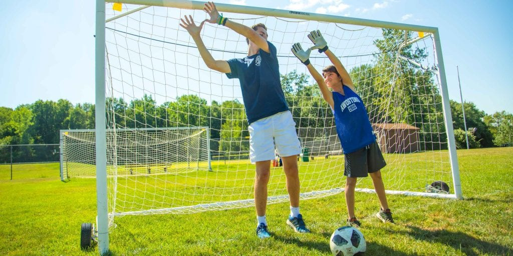 Counselor helps camper learn to be a soccer goalie