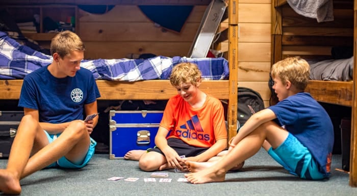 Counselor and campers play cards in cabin