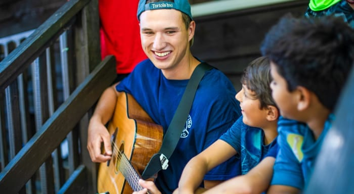 Counselor plays guitar in front of cabin