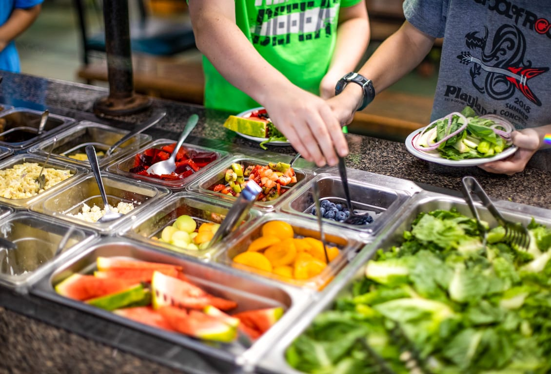 Campers get food from fruit and veggie buffet bar