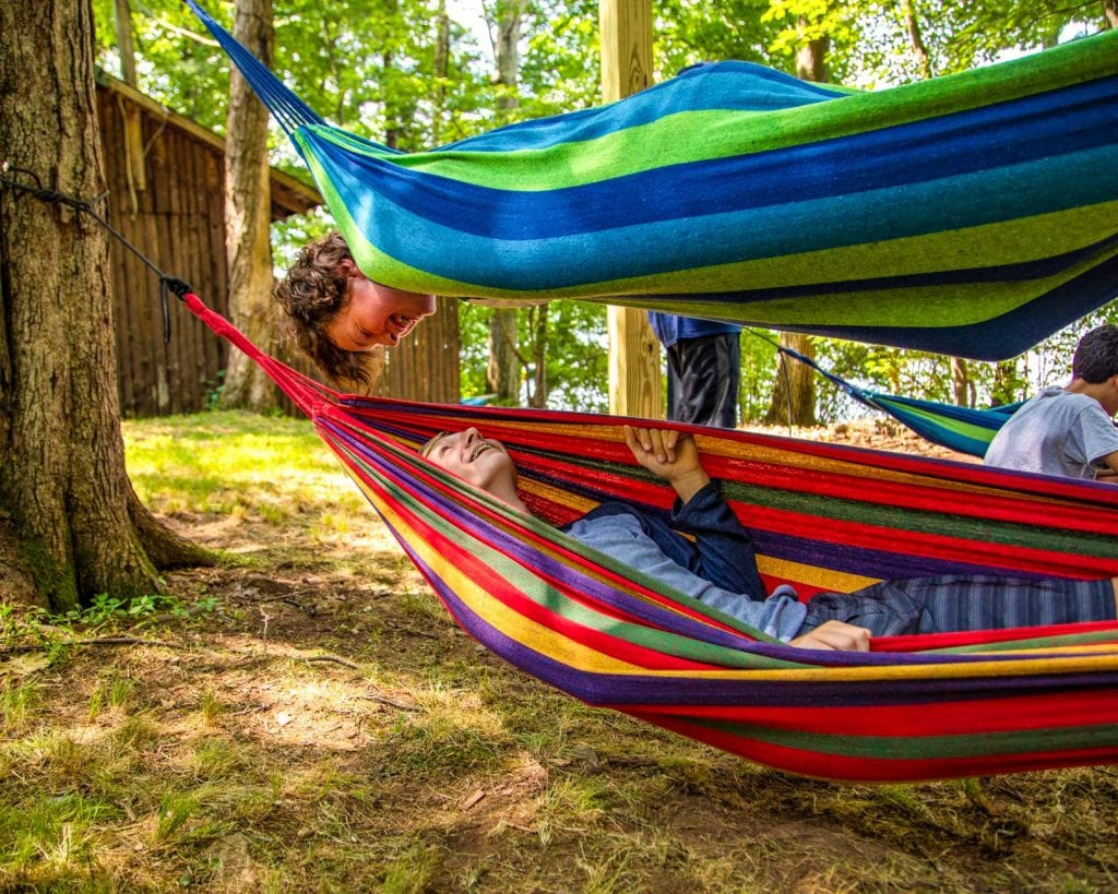 Camper in hammock flips over to look at another hammocking camper below