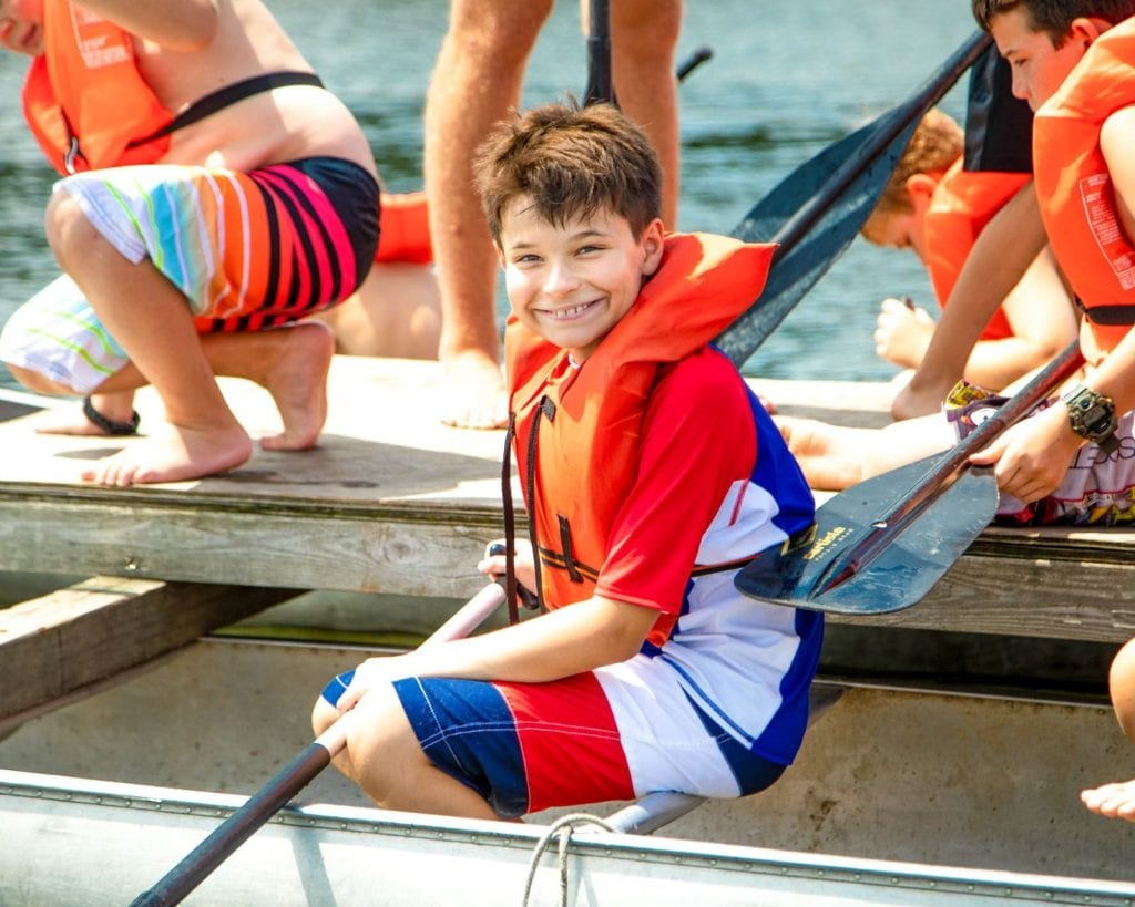 Young smiling camper sits in a metal canoe