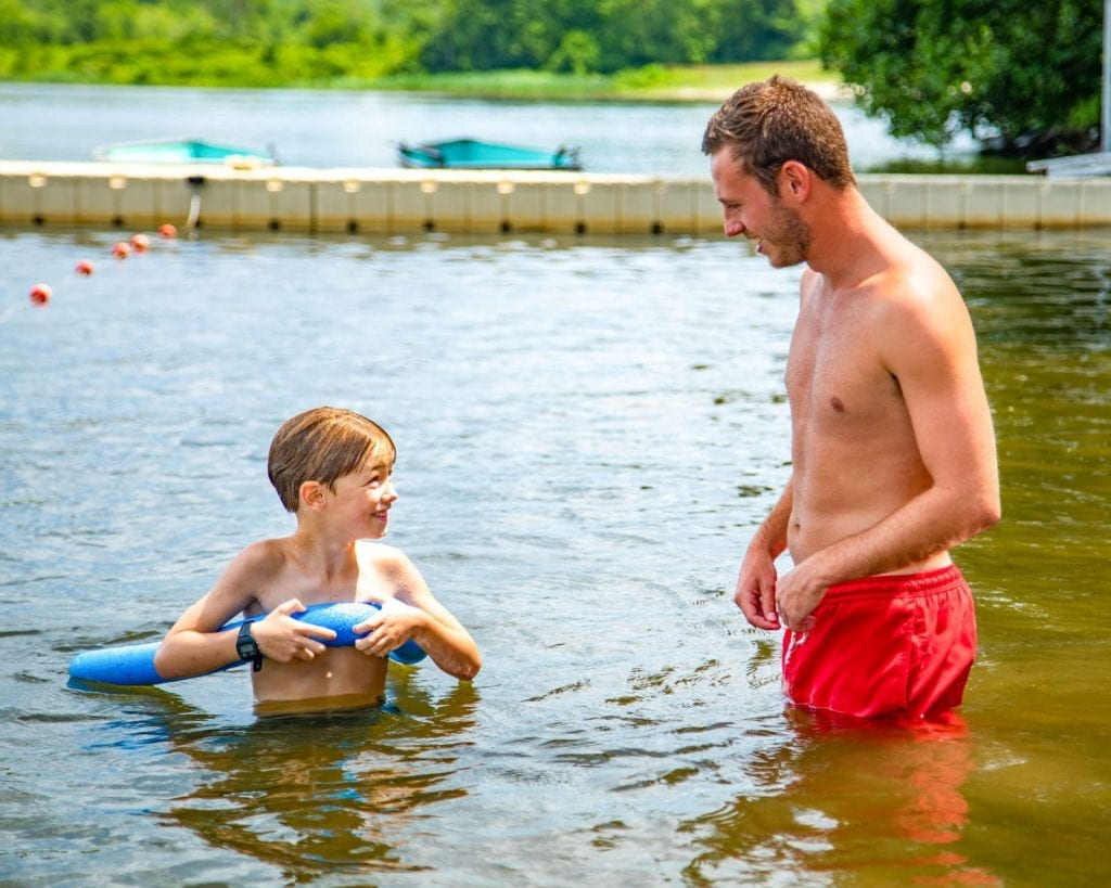Instructor helps camper swimming with a pool noodle
