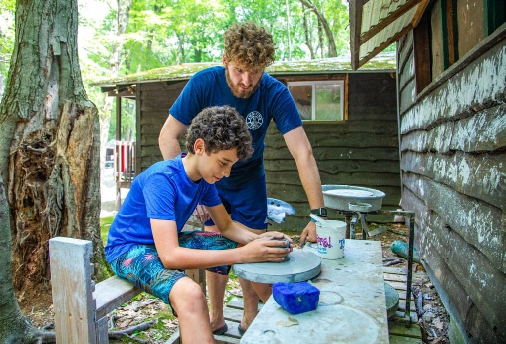 Staff member helps camper with pottery wheel
